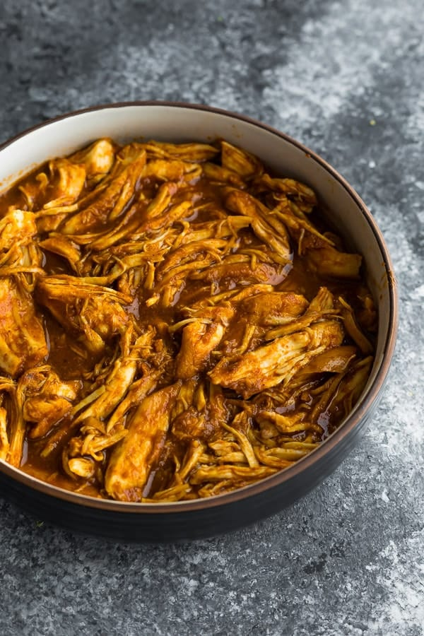 a bowl of crockpot barbecue chicken on a grey background