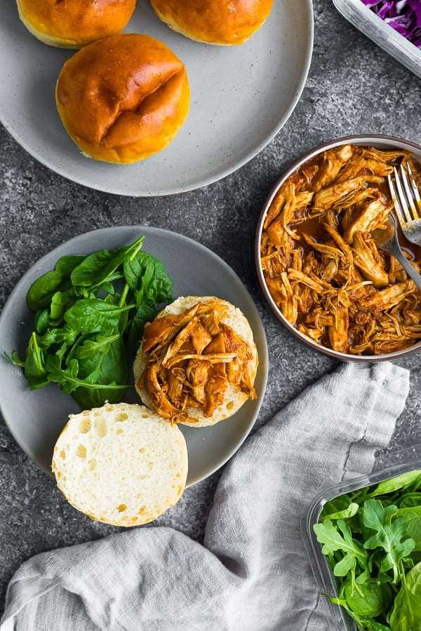 overhead shot of a table with burger buns, a bowl of the cooked crock pot bbq chicken, and a half-assembled buger