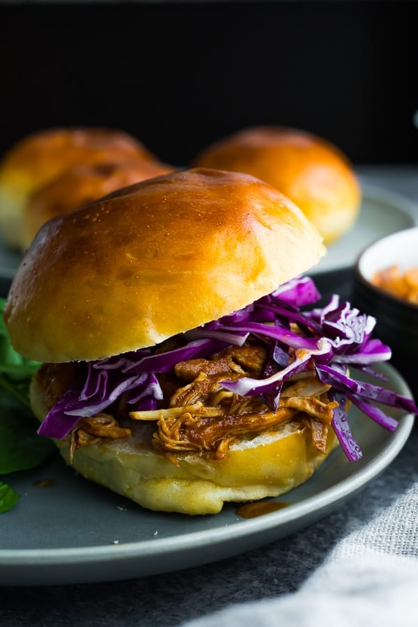 crockpot bbq chicken on a buger bun, topped with purple cabbage