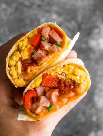 hand holding breakfast burrito cut in half