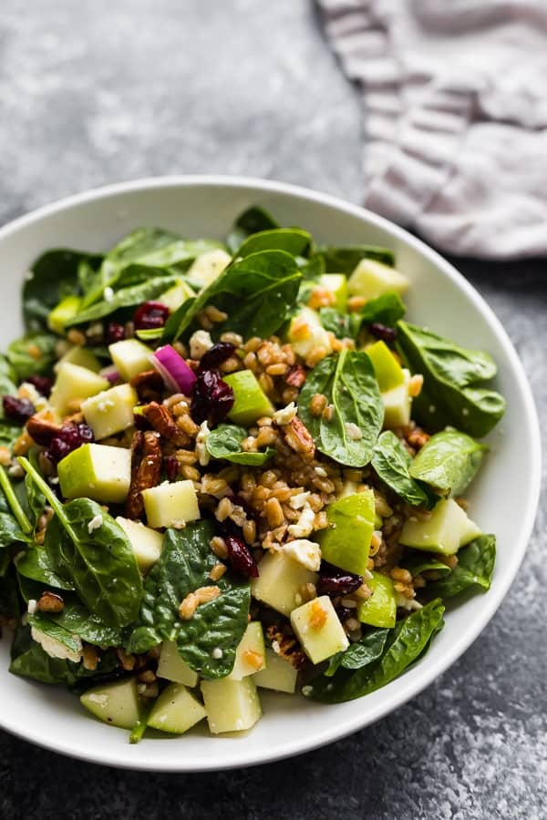 farro salad in bowl with apples, cranberries and pecans