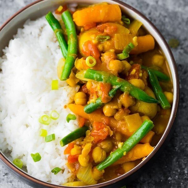 overhead shot of instant pot chickepea curry with rice and green beans in brown bowl