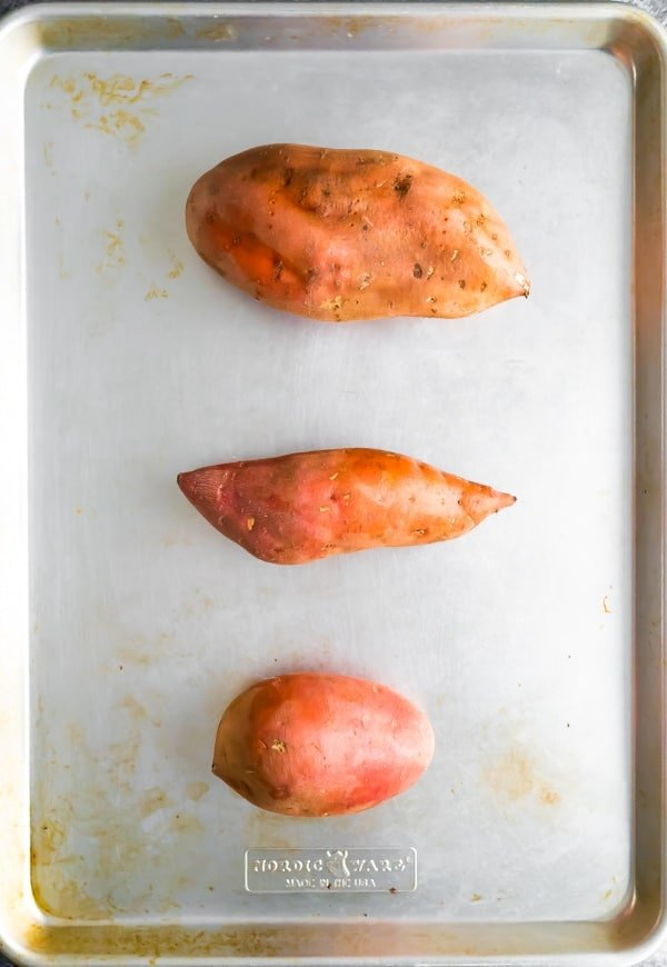 baked sweet potato recipe- different sized sweet potatoes on baking sheet before baking