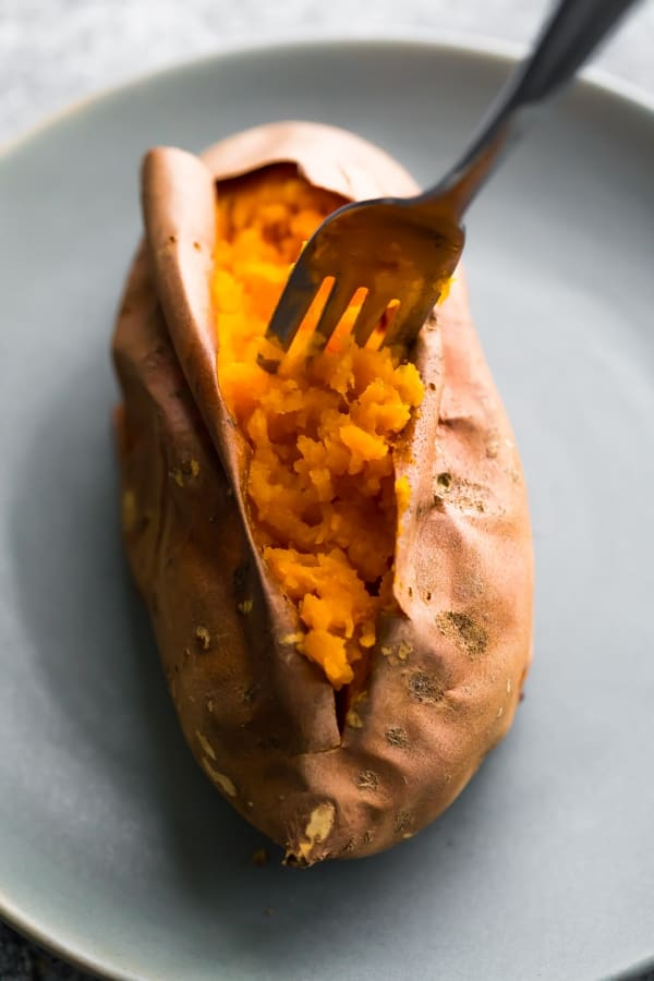 how to bake sweet potatoes- a fork fluffing tender baked sweet potato