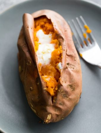 baked sweet potato with butter on gray plate with a fork