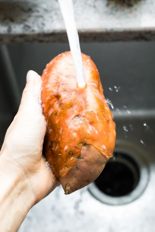 washing sweet potato under the tap for baked sweet potato recipe