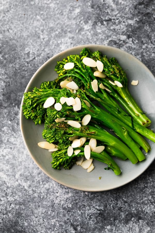 plate with sauteed broccolini with brown butter sauce and almonds