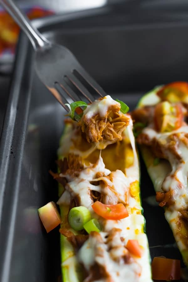 Fork scooping from the pulled pork stuffed zucchini boats