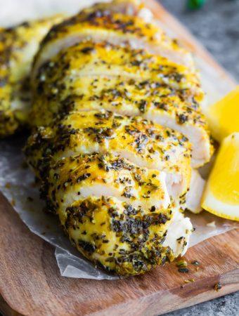 sliced lemon pepper chicken on wood cutting board with fresh lemon slices