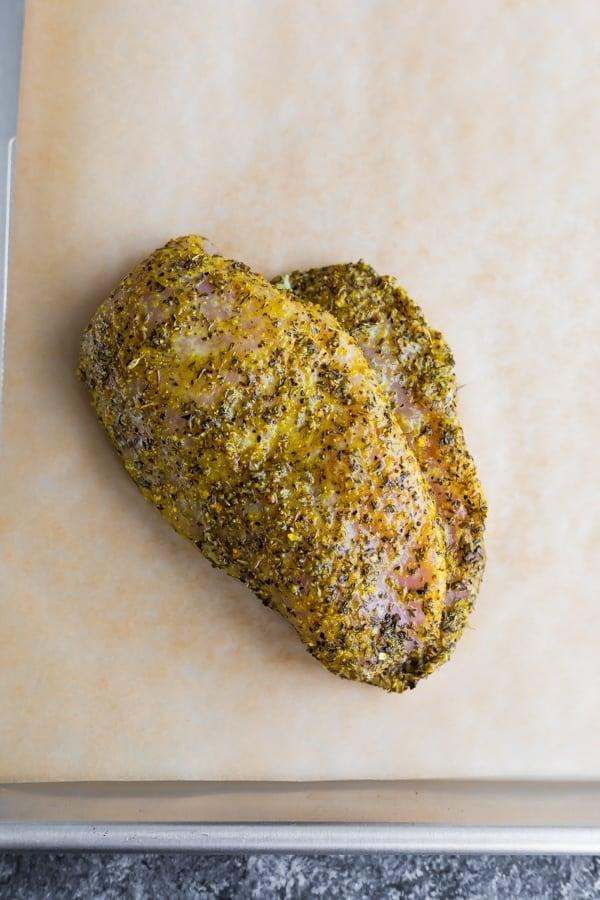 lemon pepper chicken before baking on a baking sheet
