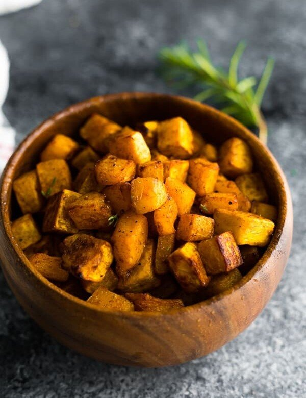 maple cinnamon roasted butternut squash in wood bowl on gray background