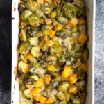 overhead shot of brussels sprouts gratin with butternut squash in white dish