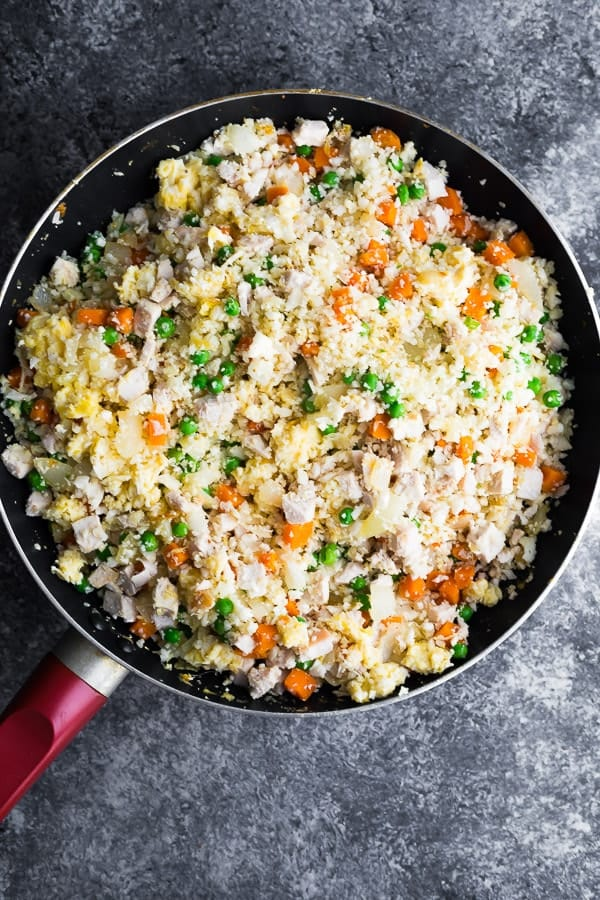 cooking the cauliflower chicken fried rice in a frying pan