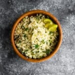 overhead shot of cilantro lime cauliflower rice in wood bowl on gray background