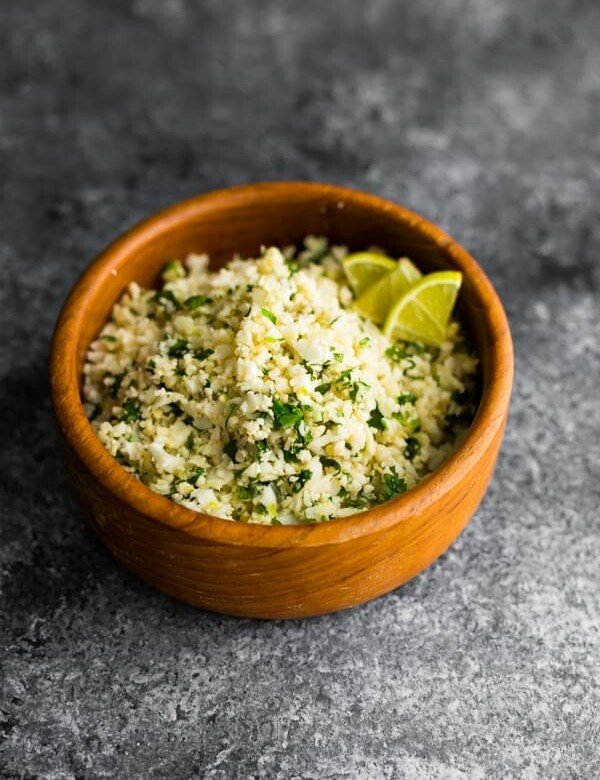 side view of cilantro lime cauliflower rice in wood bowl