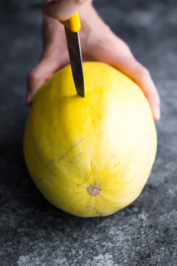 step one of how to cook spaghetti squash, poking it with a paring knife