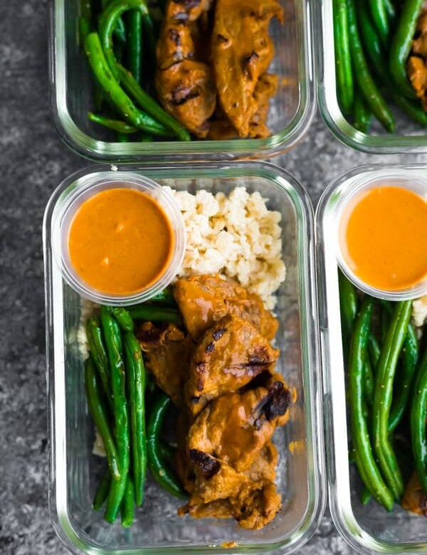 overhead shot of satay beef with green beans in four glass meal prep containers