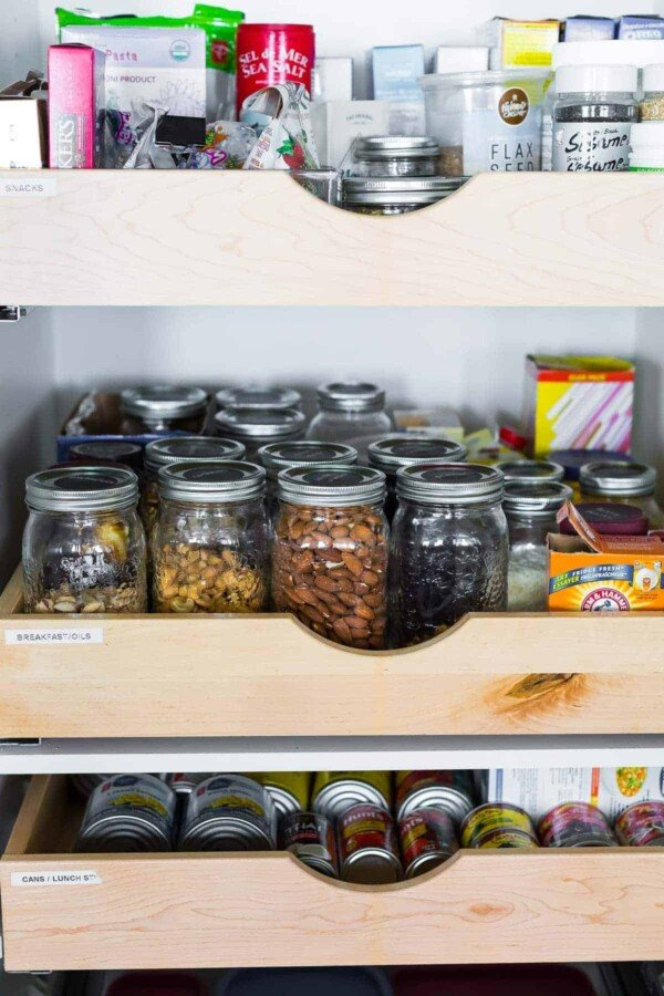 sliding shelf filled with glass mason jars filled with ingredients