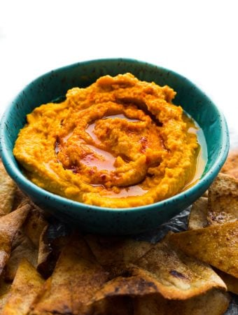 blue bowl filled with pumpkin hummus with tortillas
