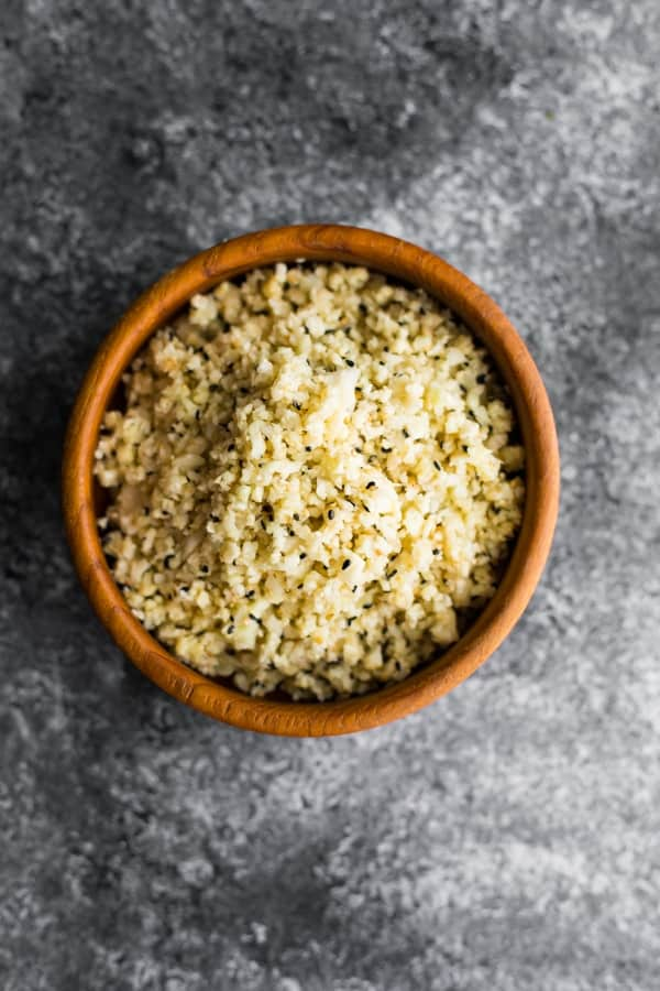 sesame ginger cauliflower rice in brown bowl