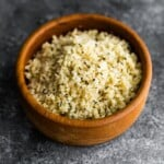 sesame ginger cauliflower rice in wood bowl on gray background