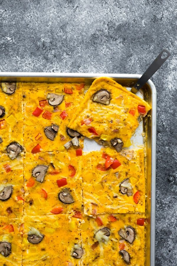 overhead shot of a spatula taking out a square of sheet pan eggs