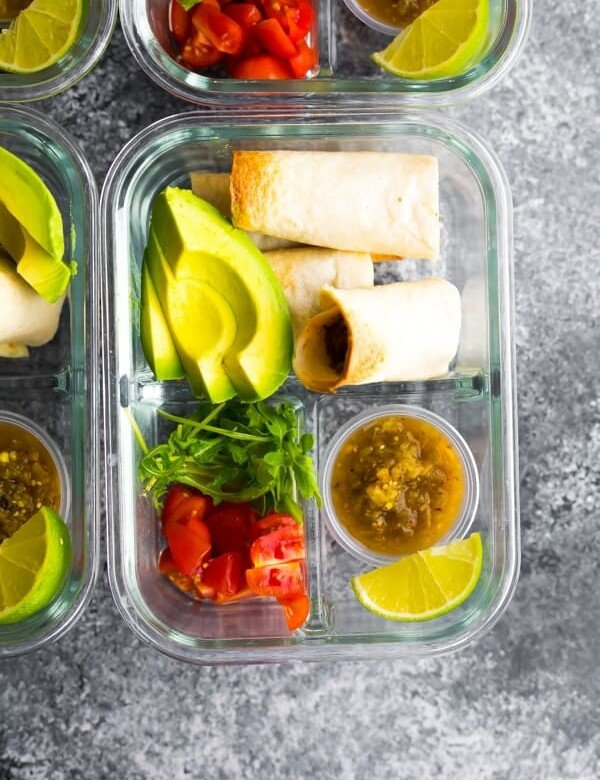 overhead shot of baked beef taquitos in glass meal prep container with fresh avocado, tomato, and lime
