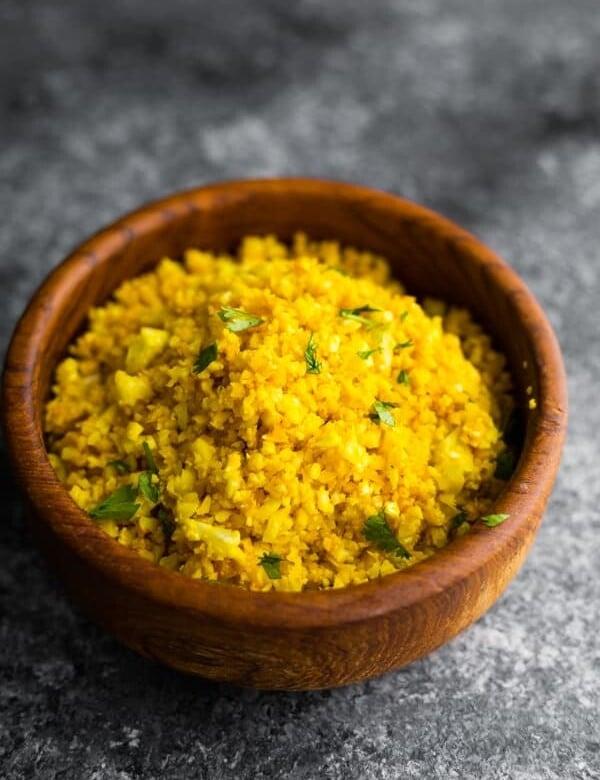 golden turmeric cauliflower rice in wood bowl on gray background
