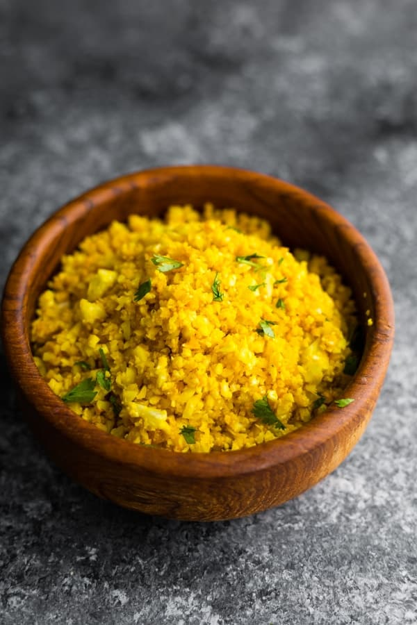 golden turmeric cauliflower rice in brown bowl