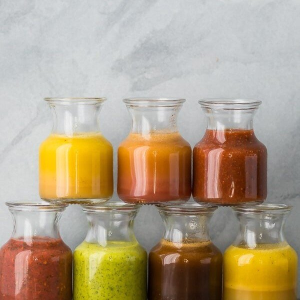 a stack of 7 glass jars filled with various vinaigrette recipes