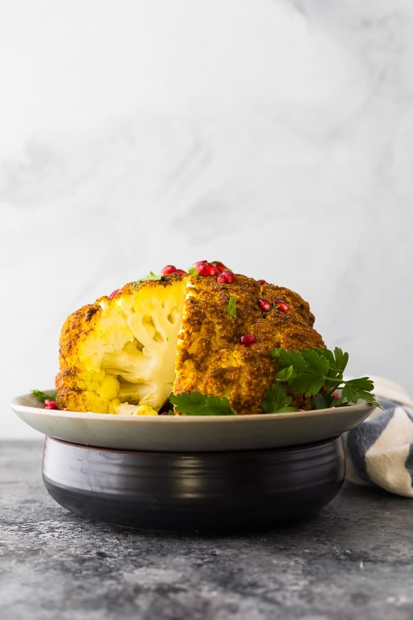 whole head roasted cauliflower with a slice cut out of it