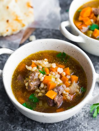 two white bowls filled with beef barley soup