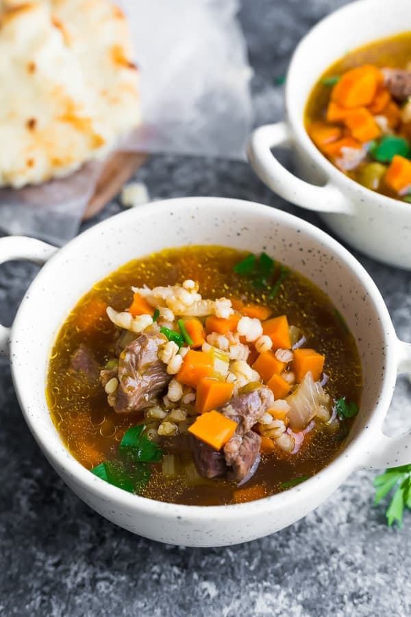 Beef barley soup in a white bowl