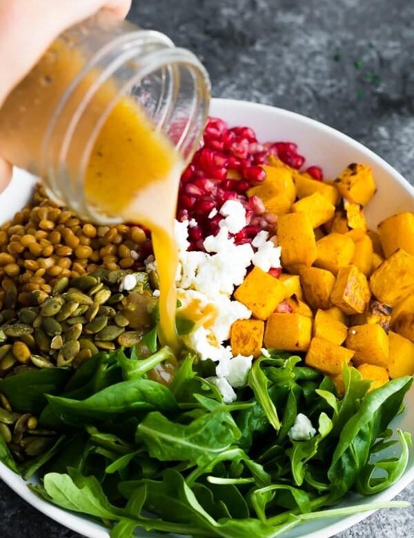 salad dressing being poured over harvest lentil salad