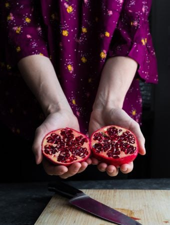 hand holding out a pomegranate cut in half