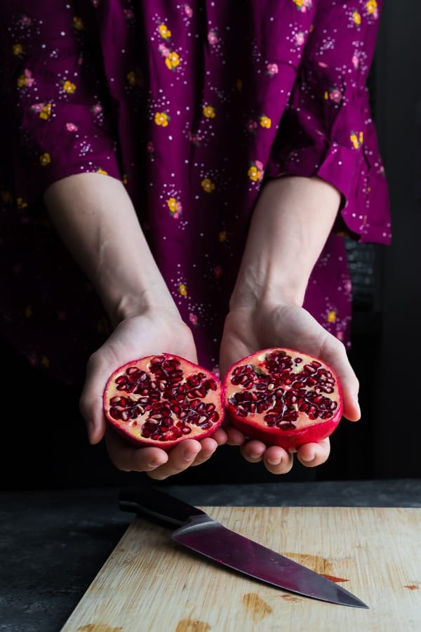 hands holding two pomegranate halves for how to cut a pomegranate