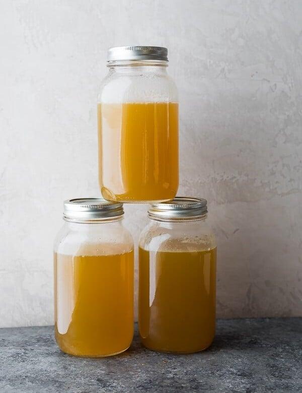 three glass stacked mason jars filled with turkey bone broth