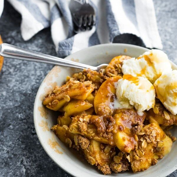 make ahead apple crisp in a white bowl with ice cream and a spoon