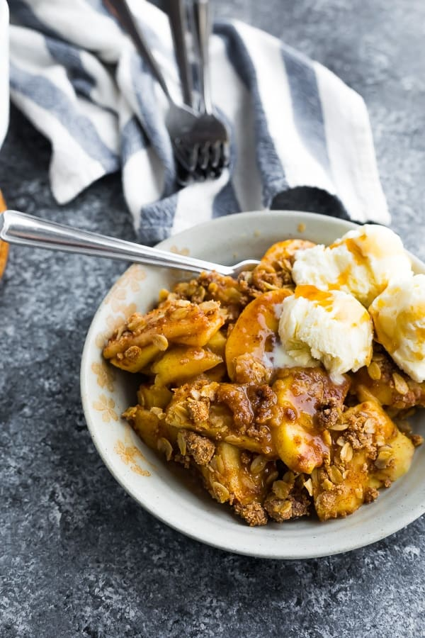 how to make apple crisp: baked apple crisp in bowl with scoops of ice cream