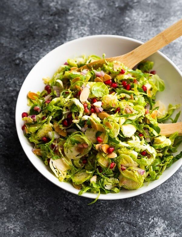overhead shot of large white bowl filled with shaved brussels sprouts salad with pomegranates