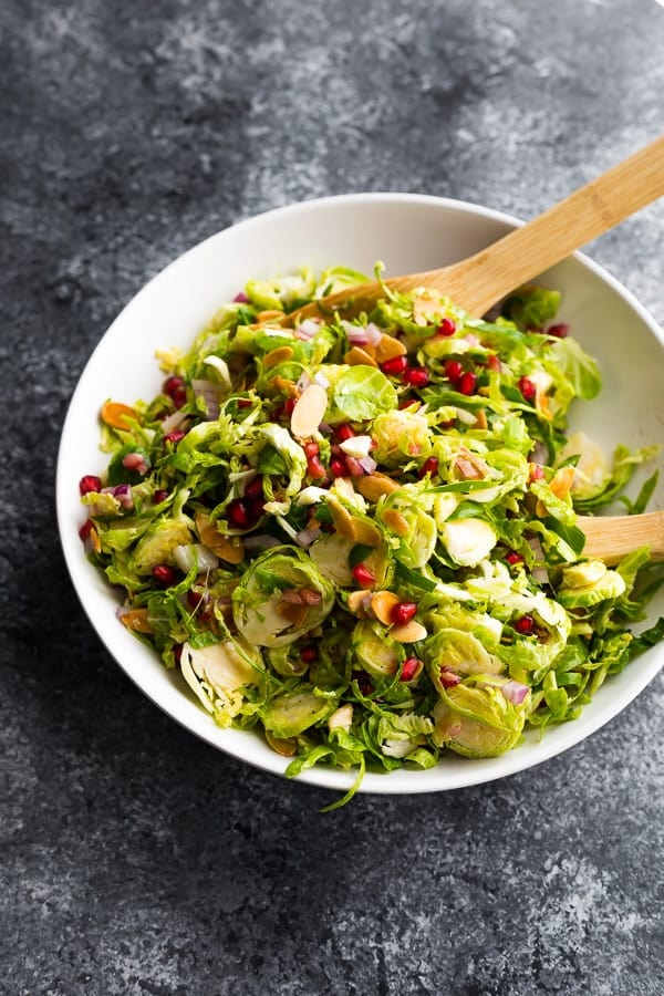 brussels sprouts salad in bowl with wooden spoons