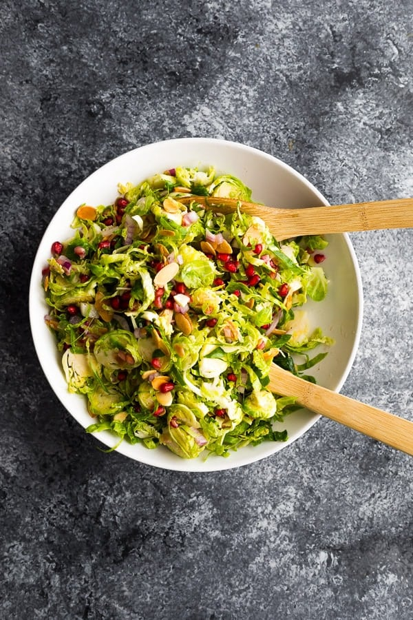 overhead shot of brussel sprouts salad in white serving bowl with tongs