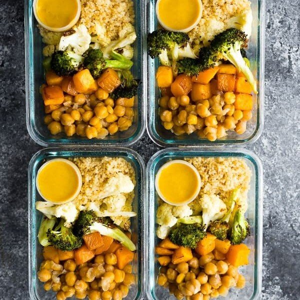 overhead shot of four glass meal prep containers filled with vegan roasted vegetables