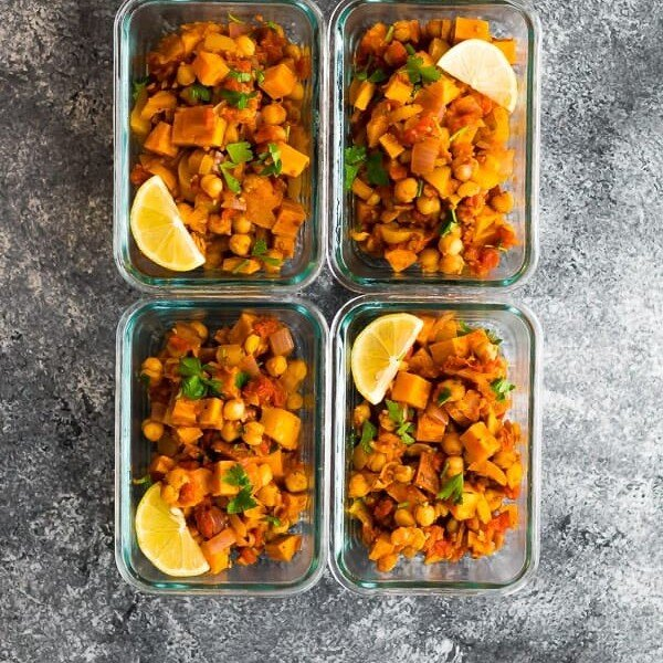 Overhead shot of four glass meal prep containers filled with vegan moroccan chickpea skillet