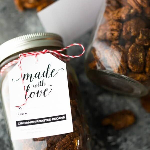 Close up shot of mason jar filled with cinnamon roasted pecans and tag saying made with love