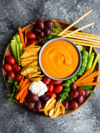 overhead shot of roasted red pepper hummus and chopped vegetables in a large bowl