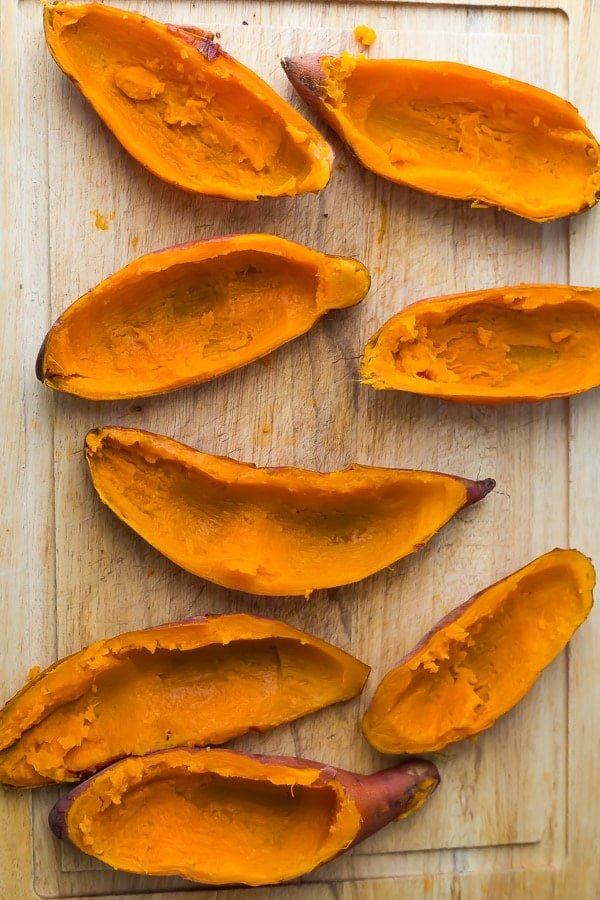 prepping the sweet potato casserole recipe by scooping out sweet potato skins