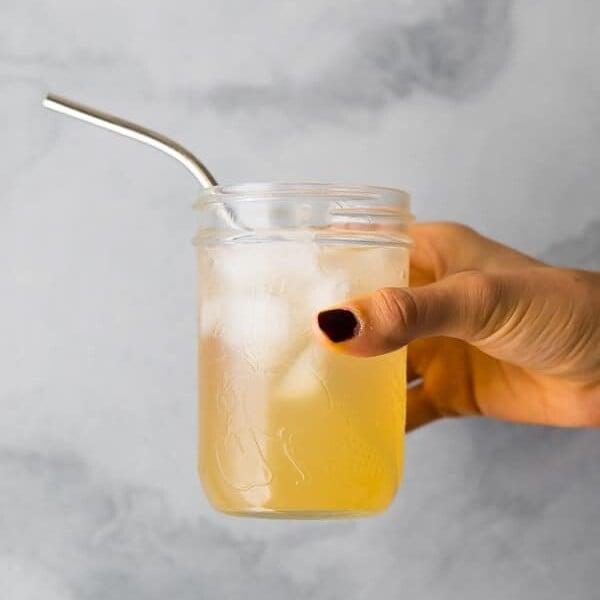 hand holding glass mason jar with apple cider vinegar drink