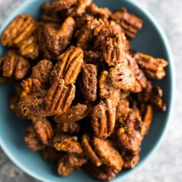 overhead shot of cinnamon roasted pecans in a blue bowl