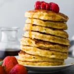 Side view of stack of cottage cheese pancakes on white plate with syrup and raspberries